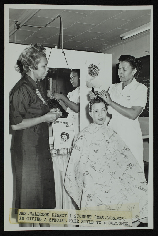Mrs. Halbrook directs a student (Mrs. Lorance) in giving a special hair style to a customer, n.d.
