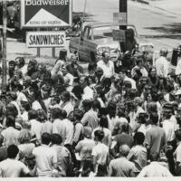 Crowd gathered in front of the Gaslight Tavern listening to speakers.  The north entrance to campus is in the background, July 22