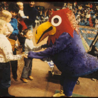 Baby Jay talking to some children during a basketball game, 1970s