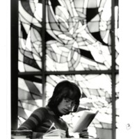 Photo of student reading on campus 1970