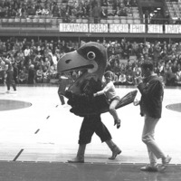 Jayhawk Mascot with a little girl riding on his tail at a basketball game, 1970