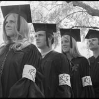 "Seniors in caps and gowns with ""Peace Dove"" armbands"