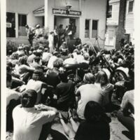 Crowd gathered in front of the Gaslight Tavern listening to speakers.  George Kimball is seated on the steps, July 19