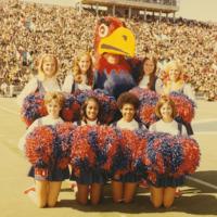 KU cheerleaders posing with the Jayhawk mascot on a football field, 1970/71