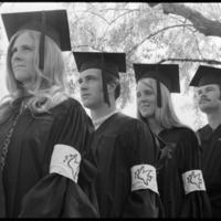 Students at commencement wearing peace dove arm bands