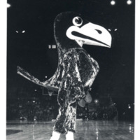 Jayhawk mascot walking the sideline during a basketball game, 1957
