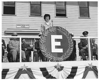 """Anne Reilly at the ceremonial presentation of the Army-Navy """"E"""" Award to the employees of Jayhawk Ordnance Works, May 2, 1944."""