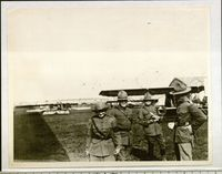 <p>Photo of Peggy Hull with officers at the airfield of the air wing attached to the artillery training camp, Le Valdahon, France, Nov., 1917.</p>